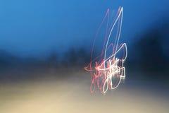 Φω'τα αυτοκινήτων στις οδούς τη νύχτα και μουτζουρωμένος Στοκ Εικόνες