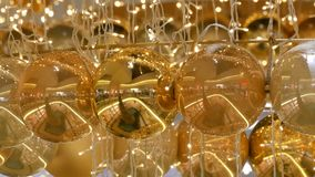 Φω'τα γιρλαντών Χριστουγέννων και σφαίρες του χρυσού χρώματος με ένα θολωμένο υπόβαθρο Νέο ντεκόρ έτους και Χριστουγέννων φιλμ μικρού μήκους