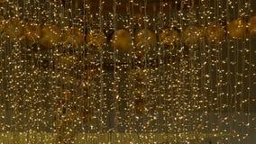 Φω'τα γιρλαντών Χριστουγέννων και σφαίρες του χρυσού χρώματος με ένα θολωμένο υπόβαθρο Νέο ντεκόρ έτους και Χριστουγέννων απόθεμα βίντεο