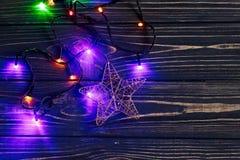 Φω'τα γιρλαντών Χριστουγέννων και χρυσό αστέρι μοντέρνο μαύρο σε αγροτικό Στοκ Φωτογραφίες