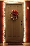 Φω'τα και στεφάνι Χριστουγέννων στη μπροστινή πόρτα τη νύχτα Στοκ εικόνα με δικαίωμα ελεύθερης χρήσης