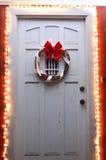 Φω'τα και στεφάνι Χριστουγέννων στη μπροστινή πόρτα τη νύχτα Στοκ Εικόνα