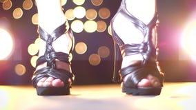 Φω'τα λάμψεων στα πόδια του θηλυκού στα παπούτσια, υψηλά τακούνια εσωτερικά, που περπατούν κοντά στη κάμερα, απεικόνιση κινήσεων φιλμ μικρού μήκους