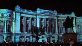Φω'τα προβολής οικοδόμησης τη νύχτα κατά τη διάρκεια του διεθνούς ελαφριού φεστιβάλ του Βουκουρεστι'ου επικέντρων φιλμ μικρού μήκους