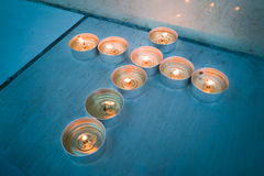 Φω'τα τσαγιού κεριών στο χριστιανικό crucifix διαγώνιο σχηματισμό Στοκ Εικόνα