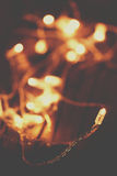 Φω'τα Χριστουγέννων πέρα από το ξύλινο υπόβαθρο Εορταστικά φω'τα, γιρλάντα στοκ εικόνα με δικαίωμα ελεύθερης χρήσης