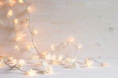 Φω'τα Χριστουγέννων που καίνε σε ένα άσπρο ξύλινο υπόβαθρο Στοκ φωτογραφία με δικαίωμα ελεύθερης χρήσης