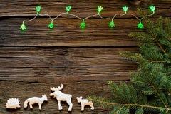 Φω'τα Χριστουγέννων σε ένα ξύλινο υπόβαθρο με ελεύθερου χώρου Μελόψωμο με μορφή των ζώων Στο υπόβαθρο των Χριστουγέννων κλαδίσκων Στοκ φωτογραφίες με δικαίωμα ελεύθερης χρήσης