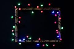 Φω'τα Χριστουγέννων σε ένα πλαίσιο στο μαύρο υπόβαθρο Χρόνος διακοπών στοκ φωτογραφία με δικαίωμα ελεύθερης χρήσης