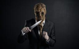 Φόβος και θέμα αποκριών: ένας βάναυσος δολοφόνος σε μια μάσκα που κρατά ένα μαχαίρι σε ένα σκοτεινό υπόβαθρο στο στούντιο στοκ εικόνες