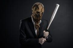 Φόβος και θέμα αποκριών: ένας βάναυσος δολοφόνος σε μια μάσκα που κρατά ένα ρόπαλο σε ένα σκοτεινό υπόβαθρο στο στούντιο στοκ εικόνες