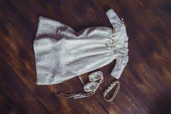 Φόρεμα και παπούτσια μωρών βαπτίσματος Κινηματογράφηση σε πρώτο πλάνο χαριτωμένου ενός νεογέννητου μικρά παπούτσια και ένα φόρεμα Στοκ φωτογραφίες με δικαίωμα ελεύθερης χρήσης