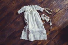 Φόρεμα και παπούτσια μωρών βαπτίσματος Κινηματογράφηση σε πρώτο πλάνο χαριτωμένου ενός νεογέννητου μικρά παπούτσια και ένα φόρεμα Στοκ Εικόνες