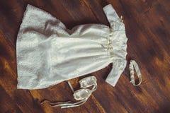 Φόρεμα και παπούτσια μωρών βαπτίσματος Κινηματογράφηση σε πρώτο πλάνο χαριτωμένου ενός νεογέννητου μικρά παπούτσια και ένα φόρεμα Στοκ Φωτογραφία