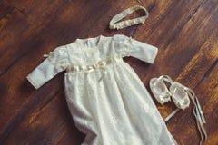 Φόρεμα και παπούτσια μωρών βαπτίσματος Κινηματογράφηση σε πρώτο πλάνο χαριτωμένου ενός νεογέννητου μικρά παπούτσια και ένα φόρεμα Στοκ φωτογραφία με δικαίωμα ελεύθερης χρήσης