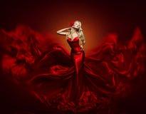 Φόρεμα μόδας γυναικών, κόκκινο τέχνης ύφασμα μεταξιού εσθήτων πετώντας κυματίζοντας Στοκ Φωτογραφίες