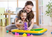 Φόρμα κοριτσιών και γυναικών παιδιών με την κινητική άμμο στο playschool ή τη φύλαξη Στοκ φωτογραφία με δικαίωμα ελεύθερης χρήσης