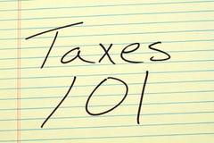 Φόροι 101 σε ένα κίτρινο νομικό μαξιλάρι Στοκ Εικόνες