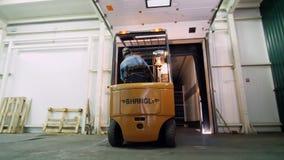 Φόρτωση ενός φορτηγού ένας εργαζόμενος σε έναν μικρό αυτόματος-φορτωτή, ηλεκτρικές forklift εισαγωγές φορτηγών, φορτώνει τα κιβώτ φιλμ μικρού μήκους