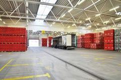 Φόρτωση των αγαθών σε μια αποθήκη εμπορευμάτων ζυθοποιείων - κλουβιά μπύρας με την μπύρα στοκ εικόνες