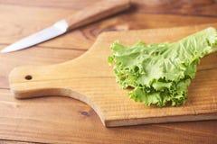Φύλλα μαρουλιού στον τέμνοντα πίνακα με το μαχαίρι στο ξύλινο υπόβαθρο στοκ εικόνες