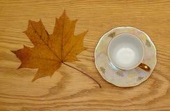 Φύλλα φθινοπώρου των διαφορετικών χρωμάτων, κοντά σε ένα όμορφο φλυτζάνι με το τσάι στοκ εικόνες