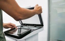 Φύλλο εγγράφου θέσεων χεριών χρήσης επιχειρηματιών στο πιάτο εκτυπωτών για τη ρύθμιση του εκτυπωτή Στοκ φωτογραφίες με δικαίωμα ελεύθερης χρήσης