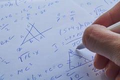 Φύλλο του εγγράφου που γεμίζουν με τους υπολογισμούς ως υπόβαθρο Προβλήματα Math στη γραφική παράσταση με το μολύβι Κάνοντας την  Στοκ Εικόνες