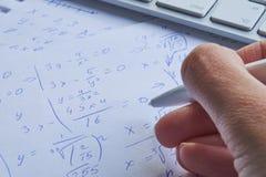 Φύλλο του εγγράφου που γεμίζουν με τους υπολογισμούς ως υπόβαθρο Προβλήματα Math στη γραφική παράσταση με το μολύβι Κάνοντας την  Στοκ Φωτογραφίες