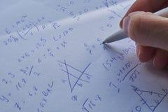 Φύλλο του εγγράφου που γεμίζουν με τους υπολογισμούς ως υπόβαθρο Προβλήματα Math στη γραφική παράσταση με το μολύβι Κάνοντας την  Στοκ Εικόνα