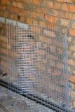 Φύλλο του πλέγματος metall με το τουβλότοιχο στο υπόβαθρο Στοκ Εικόνες