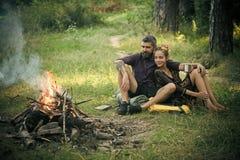 φύση αγάπης ζευγών Το ζεύγος ερωτευμένο εξετάζει την πυρά προσκόπων στο ξύλο Στοκ Φωτογραφίες