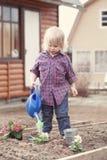 Φύτευση μικρών κοριτσιών και λουλούδια ποτίσματος στον κήπο στοκ εικόνες