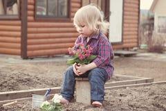 Φύτευση μικρών κοριτσιών και λουλούδια ποτίσματος στον κήπο στοκ φωτογραφία