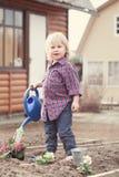 Φύτευση μικρών κοριτσιών και λουλούδια ποτίσματος στον κήπο στοκ εικόνα με δικαίωμα ελεύθερης χρήσης