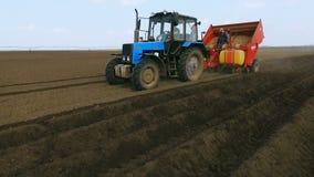 Φύτευση των πατατών με το τρακτέρ Ο καλλιεργητής στον τομέα Η εισαγωγή των μυκητοκτόνων Εναέρια άποψη 4 απόθεμα βίντεο