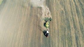 Φύτευση των σπόρων με το τρακτέρ στην άνοιξη Γεωργικός καλλιεργητής στον τομέα φιλμ μικρού μήκους