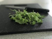 Φύλλα σαλάτας στον τεμαχίζοντας πίνακα Στοκ Φωτογραφίες