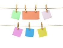 Φύλλα του εγγράφου των διαφορετικών χρωμάτων στα clothespins που συνδέονται με το α Στοκ Φωτογραφία