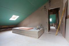 Φύλλα του ξηρού τοίχου, μέρη των υλικών σκαλωσιάς, εργαλεία λαβών και δομικό υλικό στο δωμάτιο του διαμερίσματος κατά τη διάρκεια Στοκ Φωτογραφίες
