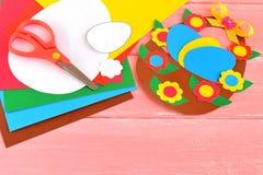 Φύλλα του χρωματισμένων εγγράφου, του ψαλιδιού, της κόλλας, του μολυβιού, του καλαθιού Πάσχας και των αυγών - που τίθενται για τη Στοκ Φωτογραφίες