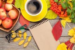 Φύλλα φθινοπώρου, φρούτα μήλων, φλυτζάνι καφέ και σημειωματάριο Στοκ Φωτογραφία
