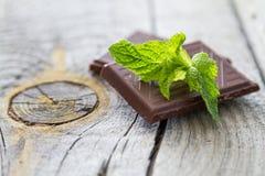Φύλλο μεντών και σοκολάτα, αγροτικό ξύλινο υπόβαθρο στοκ εικόνα με δικαίωμα ελεύθερης χρήσης