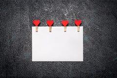 Φύλλο του εγγράφου με τους γόμφους ενδυμάτων με τις καρδιές Στοκ Φωτογραφίες