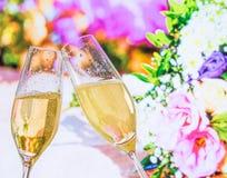 Φλάουτα CHAMPAGNE με τις χρυσές φυσαλίδες στο υπόβαθρο γαμήλιων λουλουδιών Στοκ Φωτογραφίες