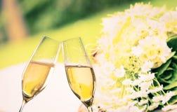 Φλάουτα CHAMPAGNE με τις χρυσές φυσαλίδες στο υπόβαθρο γαμήλιων λουλουδιών Στοκ Εικόνες