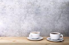 Φλιτζάνια του καφέ στον ξύλινο πίνακα κοντά στο συμπαγή τοίχο Στοκ φωτογραφία με δικαίωμα ελεύθερης χρήσης
