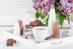 Φλιτζάνι του καφέ και λίγα μπουκάλια του γάλακτος και της σοκολάτας miklshakes Στοκ Εικόνες