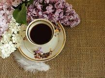 Φλιτζάνι του καφέ και ιώδη λουλούδια Στοκ φωτογραφία με δικαίωμα ελεύθερης χρήσης