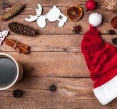 Φλιτζάνι του καφέ και καπέλο Santas, σύνολο Χριστουγέννων, δώρο και χριστουγεννιάτικο δέντρο Εορτασμός Στοκ Εικόνα